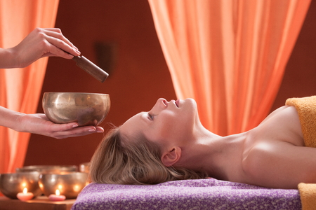 Woman in spa environment, having relaxation treatment, therapist holding Tibetan bowl LANG_EVOIMAGES