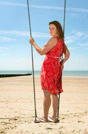 Woman standing on a swing on a beach, Zoutelande, Zeeland, Netherlands, Europe