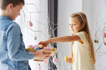 Girl and brother decorating twigs with colourful easter eggs LANG_EVOIMAGES