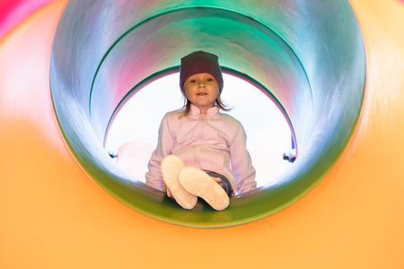 Girl in tube on climbing frame looking at camera smiling LANG_EVOIMAGES