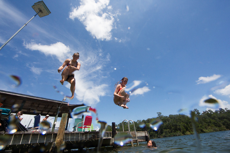 Teenagers jumping into lake, low angle view LANG_EVOIMAGES