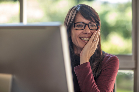 Happy businesswoman with hand on face at home desk