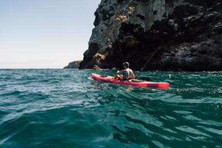 Young male sea kayaker fishing near cliff, Santa Cruz Island, California, USA