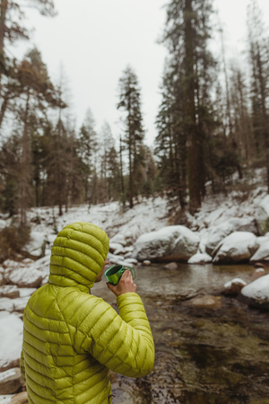 Male hiker looking drinking coffee while out at river in snowy Sequoia National Park, California, USA LANG_EVOIMAGES