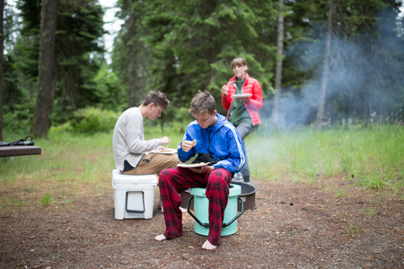 Family in rural setting, camping, eating meal