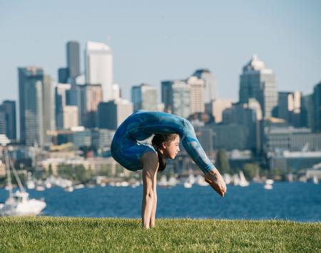 Teenage girl outdoors, balancing on hands in yoga position
