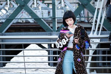 Stylish young woman looking at smartphone on millennium footbridge, London, UK