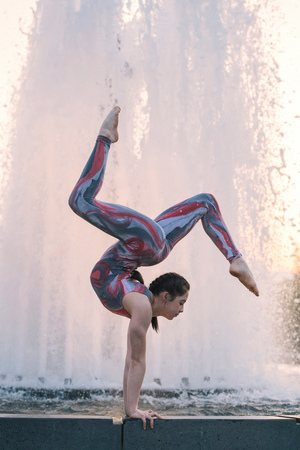 Teenage girl beside fountain, balancing on hands in yoga position LANG_EVOIMAGES