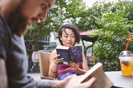Multi ethnic hipster couple reading books at sidewalk cafe, Shanghai French Concession, Shanghai, China LANG_EVOIMAGES