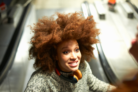Young woman on escalator, smiling, elevated view