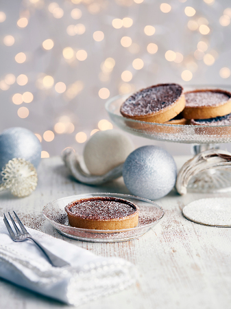 Christmas tarts dusted with sugar, Christmas baubles beside them