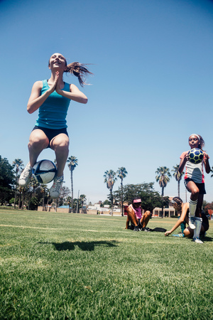 Schoolgirl jumping with soccer ball on school sports field LANG_EVOIMAGES