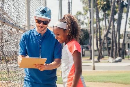 Teacher with clipboard talking to teenage schoolgirl soccer player on school sports field