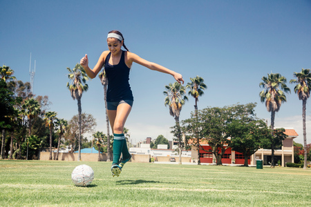 Schoolgirl soccer player kicking ball on school sports field