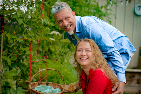 Portrait of mature gardening couple by tomato plants in garden LANG_EVOIMAGES