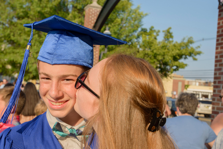 Girl kissing boy on cheek at graduation ceremony
