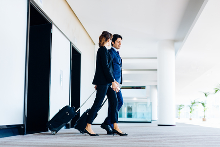 Businessman and businesswoman with wheeled luggage exiting hotel escalators LANG_EVOIMAGES