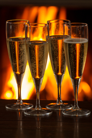 Four filled champagne glasses on table in front of burning fire LANG_EVOIMAGES