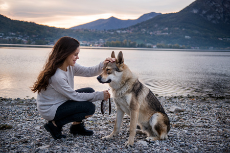 Young woman petting dog on riverbank, Vercurago, Lombardy, Italy LANG_EVOIMAGES