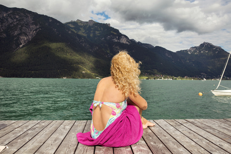 Rear view of woman sitting on pier looking away at view, Innsbruck, Tirol, Austria, Europe LANG_EVOIMAGES