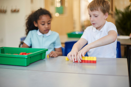 Schoolboy and girl constructing toy blocks in classroom at primary school LANG_EVOIMAGES
