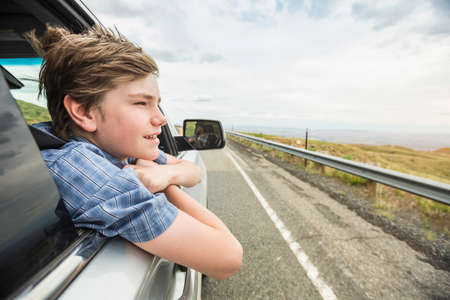 Boy on road trip leaning out of car window LANG_EVOIMAGES