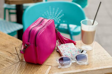 Handbag, sunglasses and latte on sidewalk cafe table