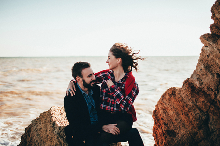 Romantic mid adult couple sitting on beach rock, Odessa Oblast, Ukraine LANG_EVOIMAGES