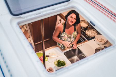 Portrait of young woman through yacht hatch preparing food in kitchen, Croatia