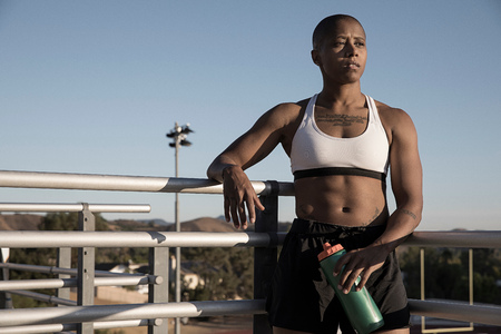 Portrait of woman wearing sports clothing holding water bottle LANG_EVOIMAGES