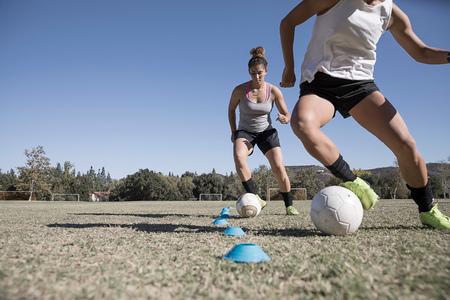 Women dribbling footballs LANG_EVOIMAGES