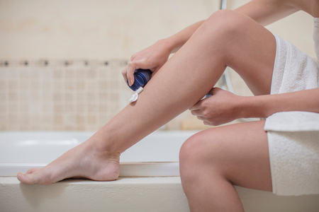 Young woman applying shaving foam to leg in bathroom, cropped