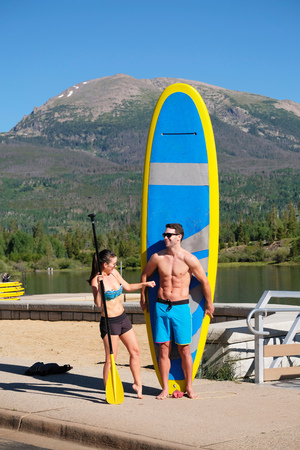 Paddleboarding couple with paddleboard on lake shore, Frisco, Colorado, USA LANG_EVOIMAGES