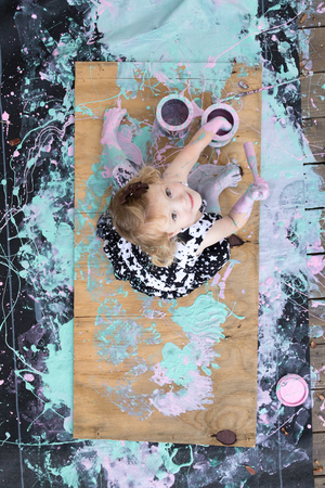 Overhead view of girl covered in paint sitting on painting looking up LANG_EVOIMAGES