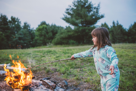Young girl toasting marshmallow in fire