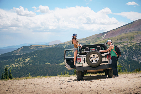 Road trip couple unpacking four wheel convertible in Rocky mountains, Breckenridge, Colorado, USA LANG_EVOIMAGES