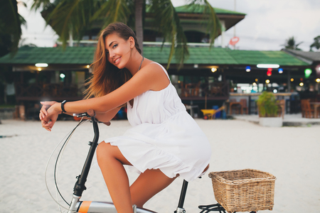 Portrait of young woman leaning on bicycle handlebars on sandy beach, Krabi, Thailand