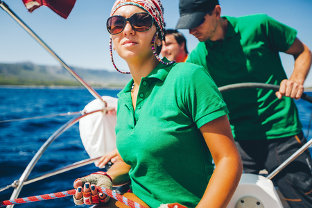 Young woman and men yachting near coast, Croatia LANG_EVOIMAGES