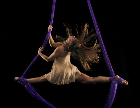 Young female aerial acrobat doing the splits with feet wrapped in silk rope against black background