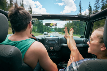 Young woman with feet up driving on road trip with boyfriend, Breckenridge, Colorado, USA LANG_EVOIMAGES