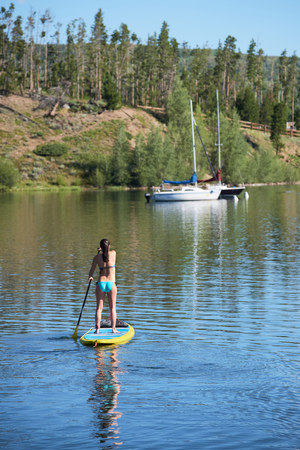 Rear view of young woman stand up paddleboarding on lake, Frisco, Colorado, USA LANG_EVOIMAGES