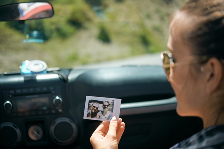 Over shoulder view of young woman on road trip holding instant photograph with boyfriend, Breckenridge, Colorado, USA