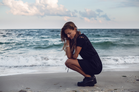 Young woman crouching by waters edge on beach, Odessa, Odessa Oblast, Ukraine LANG_EVOIMAGES