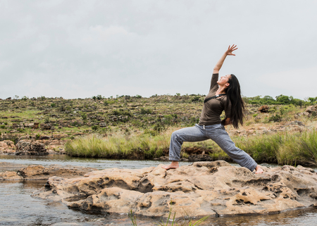 Young female tourist practicing warrior yoga pose at Bourkes Potholes, Mpumalanga, South Africa