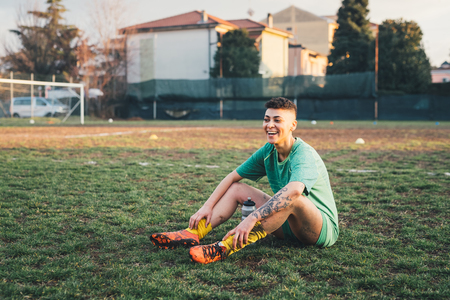 Football player taking break on pitch LANG_EVOIMAGES