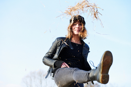 Woman in cap kicking up straw against blue sky