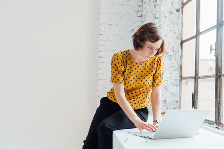 Businesswoman sitting on windowsill using laptop LANG_EVOIMAGES