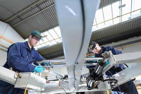 Apprentice engineers working on locomotive pantograph in train engineering factory LANG_EVOIMAGES