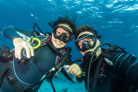 Underwater portrait of couple scuba diving at the Tubbataha Reefs Natural Park, Cagayancillo, Palawan, Philippines