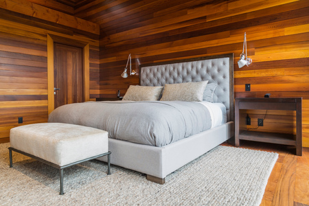 King size bed in master bedroom inside luxurious cedar wood home LANG_EVOIMAGES